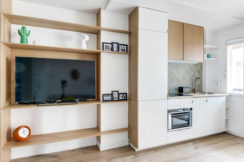 Voltaire apartment 3 - Small studio apartment uses see-through shelving as an elegant partition wall
