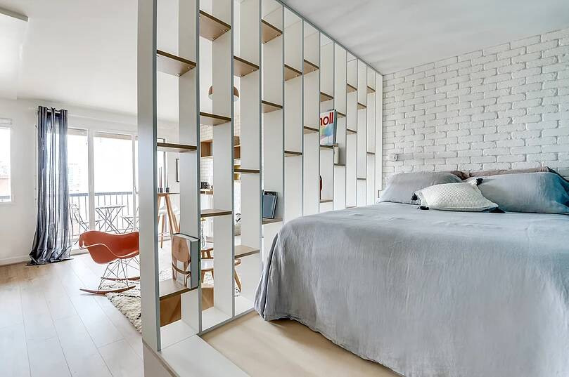 Voltaire apartment 7 - Small studio apartment uses see-through shelving as an elegant partition wall